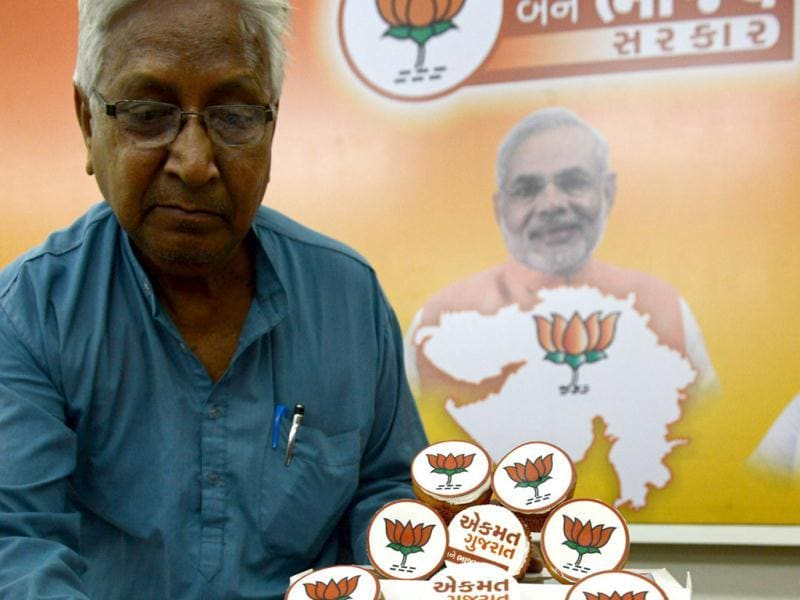 Bharatiya Janta Party (BJP) media coordinator Ambala Koshti poses with cupcakes made by a party supporter at the BJP headquarters in Ahmedabad. (AFP Photo)