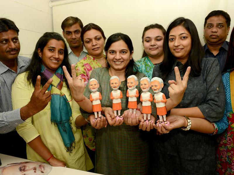 Supporters of the Gujarat chief minister Narendra Modi pose with clay figurines of the politician called 'Icon Tops' in Ahmedabad. (AFP Photo)