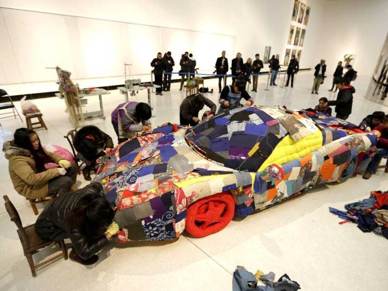 Women sew an art work based on a sports car model by Danish artist Erik A on the outskirts of Beijing. Reuters