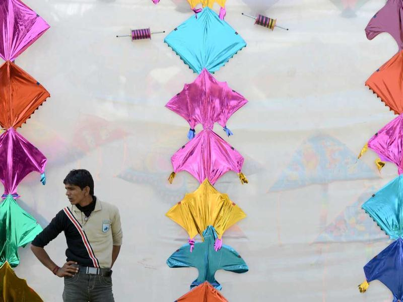 An Indian tea vendor stands in front of a display during the Delhi International Kite Festival 2012 on the lawns of the India Gate monument in New Delhi. (AFP Photo)