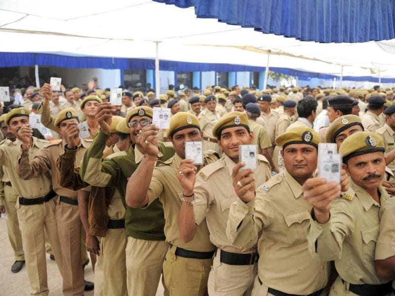 Gujarat state police and home guard officials pose with their voter identity cards at The Postal Ballot Issue Centres at the police headquarters (HQ) in Ahmedabad. AFP/Sam Panthaky