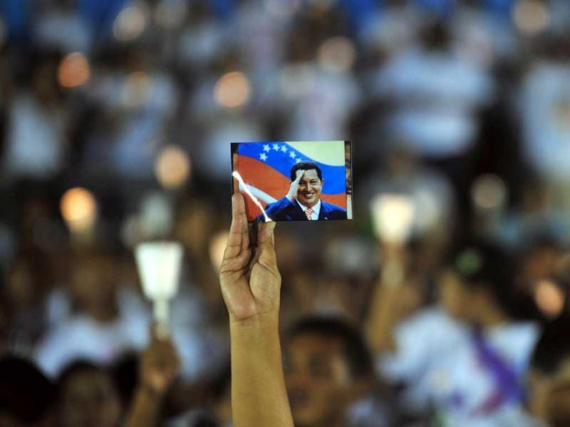 A person holds a photograph of Hugo Chavez during a ceremony held in Managua to pray for the health of Hugo Chavez. AFP Photo