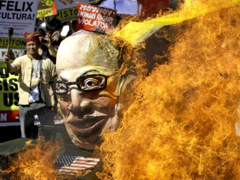 Protesters burn an effigy of Philippine President Benigno Aquino III on board a mock tank as they commemorate International Human Rights Day near the Presidential Palace in Manila, Philippines. The group called the Aquino administration as alleged human rights violators. (AP Photo/Aaron Favila)