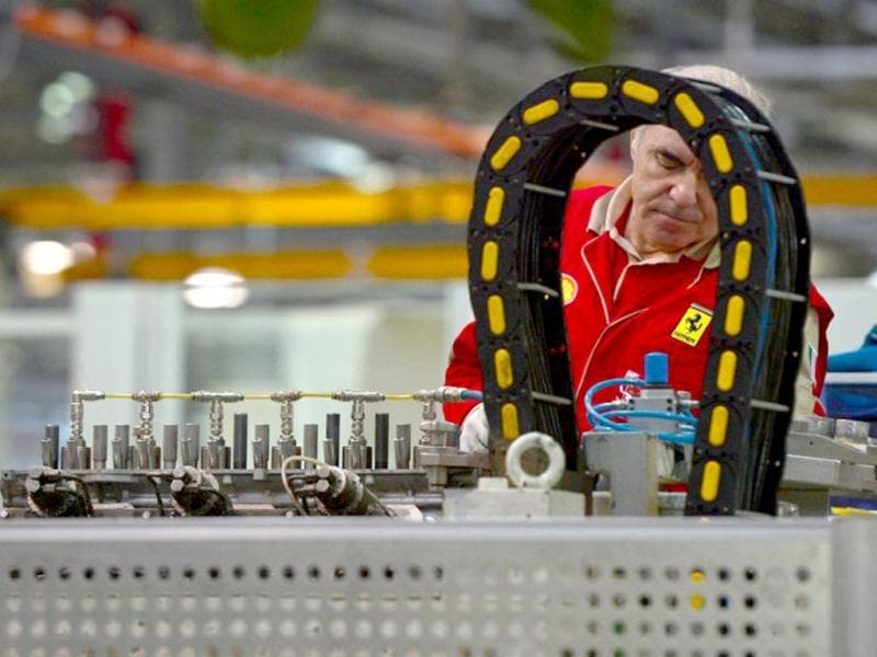 An employee works on an engine in the Ferrari factory in Maranello. The Ferrari 45 buildings's factory, where more than 3,000 workers produce the company's GT and Formula 1 cars is based in Maranello. AFP Photo