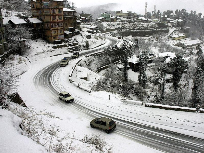 Vehicles ply on a snow covered road during season's first snowfall at Kufri near Shimla. PTI