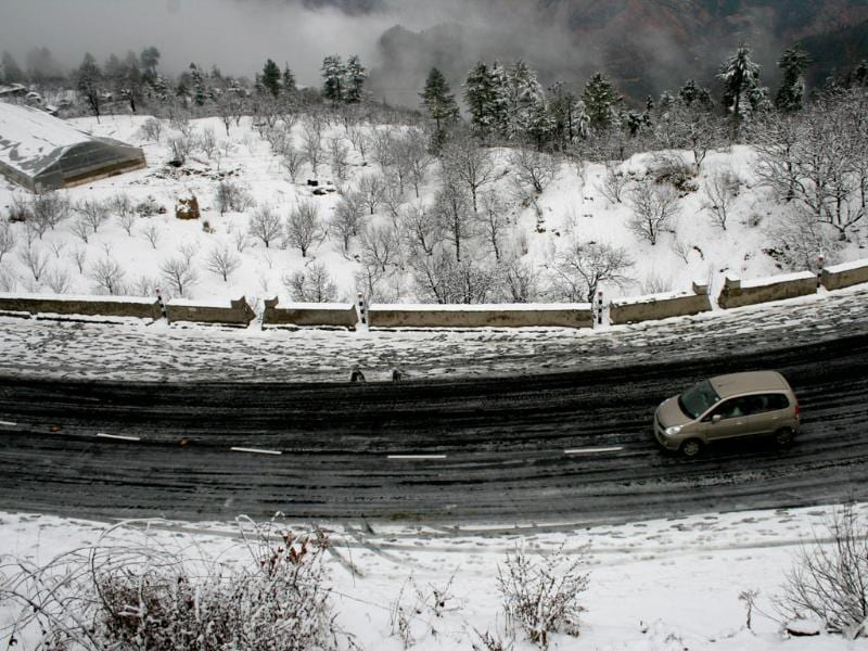 A car plying on National Highway - 22 after season's first snow fall at Kufri, in Shimla. HT/Santosh Rawat