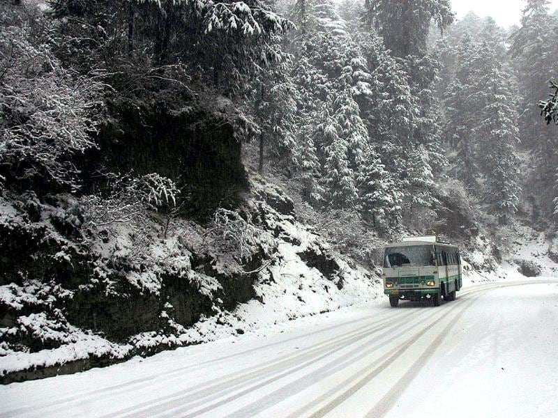 A Himachal Road Transport Corporation bus moves slowly on a snow covered road during season's first snowfall at Kufri near Shimla. PTI