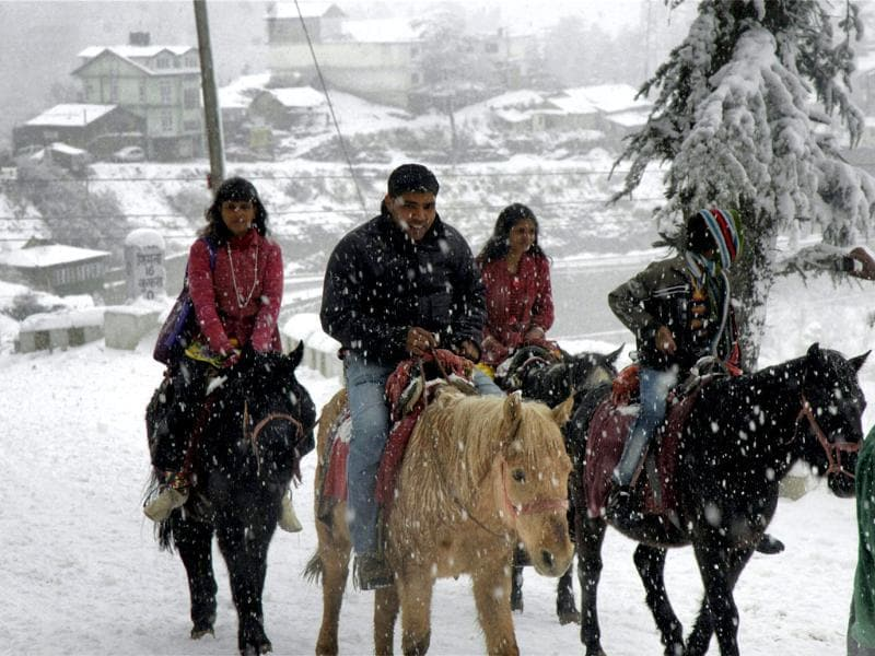 Tourists enjoy a horse ride during season's first snowfall at Kufri near Shimla. PTI