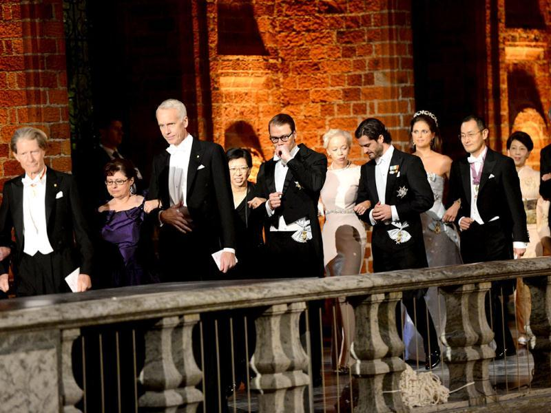 The 2012 Nobel prize laureates arrive with Prince Carl Philip of Sweden (5thR) and Prince Daniel of Sweden (5thL) at the Stockholm Town Hall to attend the Nobel banquet, a traditional dinner after the Nobel Prize awarding ceremony at the Stockholm City Hall. AFP PHOTO/JONATHAN NACKSTRAND
