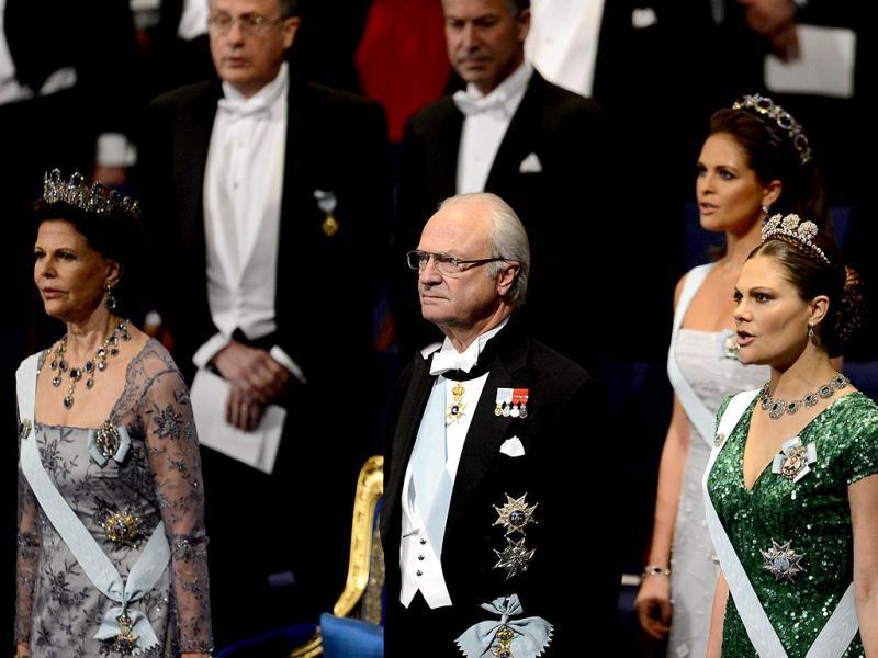 Queen Silvia of Sweden (2dL) and King Carl Gustaf of Sweden (L), Princess Victoria of Sweden (R) and Princess Madeleine of Sweden (2d row R) sing the national anthem at the start of the Nobel prize awarding ceremony at the Stockholm Concert Hall in Stockholm, Sweden. AFP PHOTO/JONATHAN NACKSTRAND