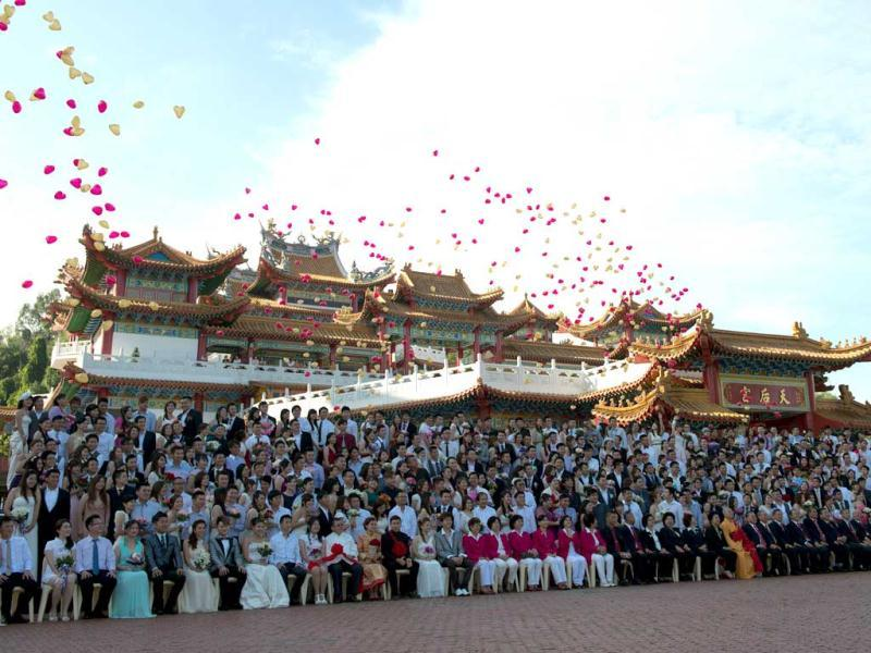 Baloons fly in air as newlywed couples celebrate their mass wedding in conjunction with the date 12.12.12 outside a Chinese temple in Kuala Lumpur. Some 200 couples gathered at the temple to attend a grand colourful wedding ceremony. (AFP Photo)