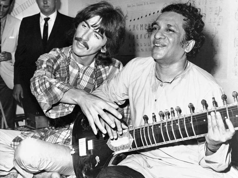 In this Aug. 3, 1967 file photo, George Harrison, of the Beatles, left, sits cross-legged with his musical mentor, Ravi Shankar, in Los Angeles, as Harrison explains to newsmen that Shankar is teaching him to play the sitar. Shankar, the sitar virtuoso who became a hippie musical icon of the 1960s after hobnobbing with the Beatles and who introduced traditional Indian ragas to Western audiences over an eight-decade career, died Tuesday, Dec. 11, 2012. He was 92. (AP Photo)