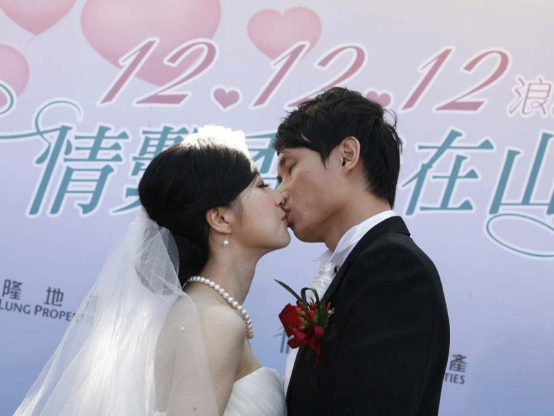 A couple kiss during a mass wedding ceremony at the Peak in Hong Kong. At least 700 couples are expected to get married in the date 12/12/12, the last such triple-date in this year in Hong Kong as they believe the date will bring them everlasting love. (AP Photo)