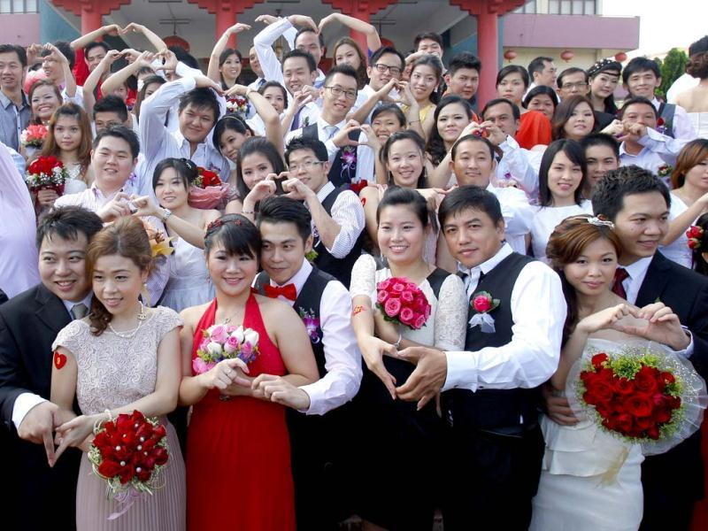 Newly wed couples pose at a photo session during a mass wedding ceremony at the Hokkien Association building in Klang, outside Kuala Lumpur, Malaysia. Over 200 brides and grooms attended the ceremony to mark the unique date of 12-12-12. (AP Photo)