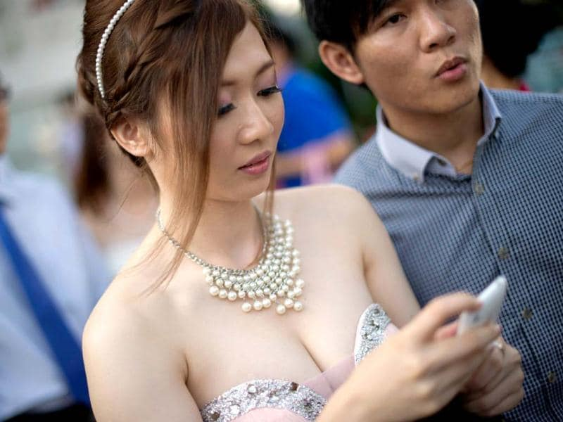 A bride checks her messages while getting ready for a group picture after their mass wedding in conjunction with the date 12.12.12 outside a Chinese temple in Kuala Lumpur. Some 200 couples gathered at the temple to attend a grand colourful wedding ceremony on a unique day, which many in Asia marks an auspicious date on the calendar. (AFP Photo)
