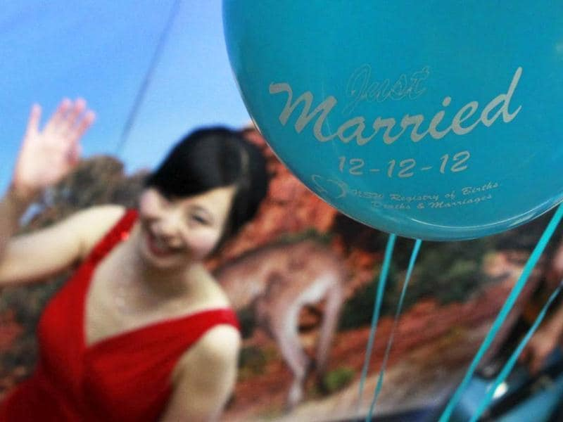 Shudi Tang, walks past a balloon commemorating her wedding on 12/12/12 as she leaves a marriage office in central Sydney. A record number of couples are getting married today in Australia in celebration of the last time for almost 90 years that the date will have the same number for the day, month and year. (Reuters Photo)