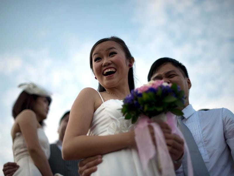 A newlywed couple celebrates after a mass wedding in conjunction with the date 12.12.12 outside a Chinese temple in Kuala Lumpur. (AFP Photo)