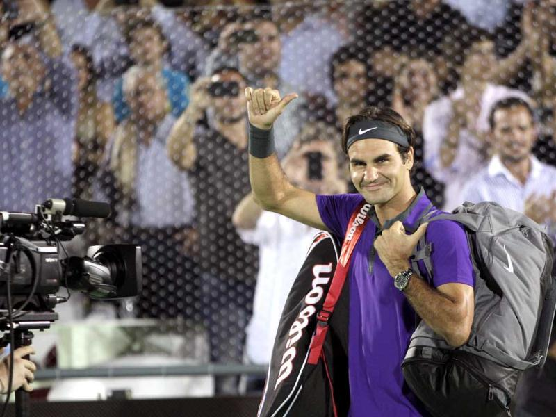 Swiss tennis player Roger Federer waves as he enters the court before an exhibition match against Argentina's Juan Martin Del Potro in Buenos Aires, Argentina. AP