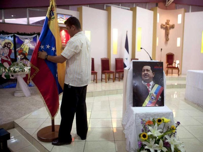 A man prepares a Venezuelan flag next to an image of Venezuela's President Hugo Chavez before a mass in support of him in Managua, Nicaragua. AP