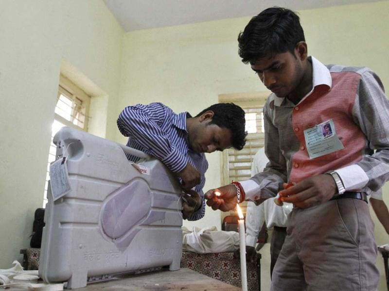 Polling officials seal an Electronic Voting Machine (EVM) at the end of polls at a polling station after the first phase of state elections at Viramgam town in Gujarat. Reuters Photo