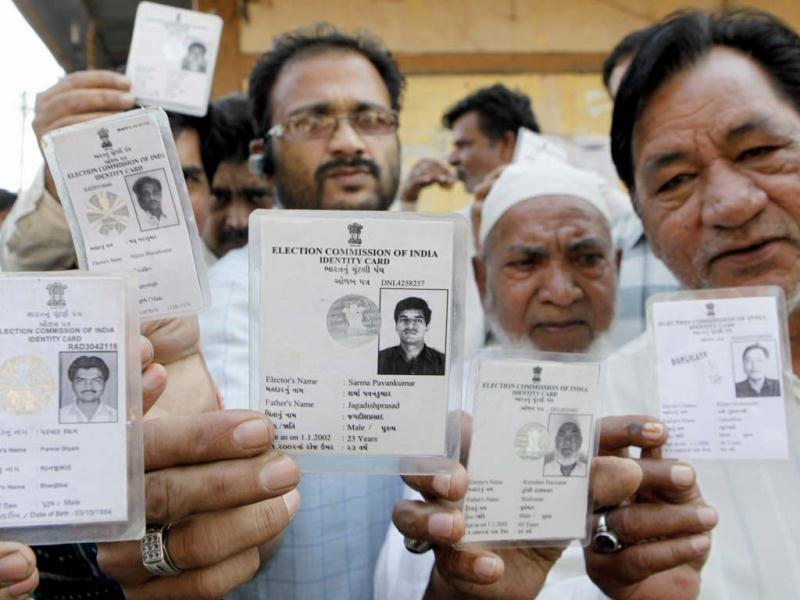 People flash their voters' card during the first phase polling of Gujarat assembly election in Surat, Gujarat. HT/Satish Bate
