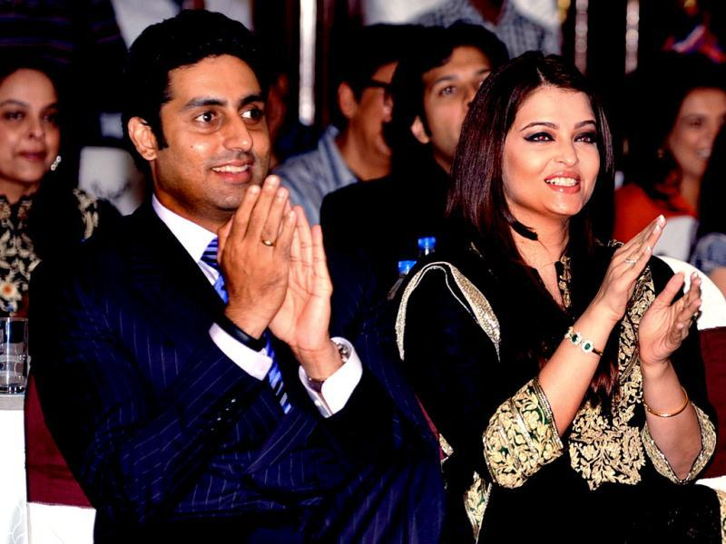 Abhishek Bachchan and Aishwarya Rai Bachchan enjoy the event as they sit next to eachother. (AFP Photo)