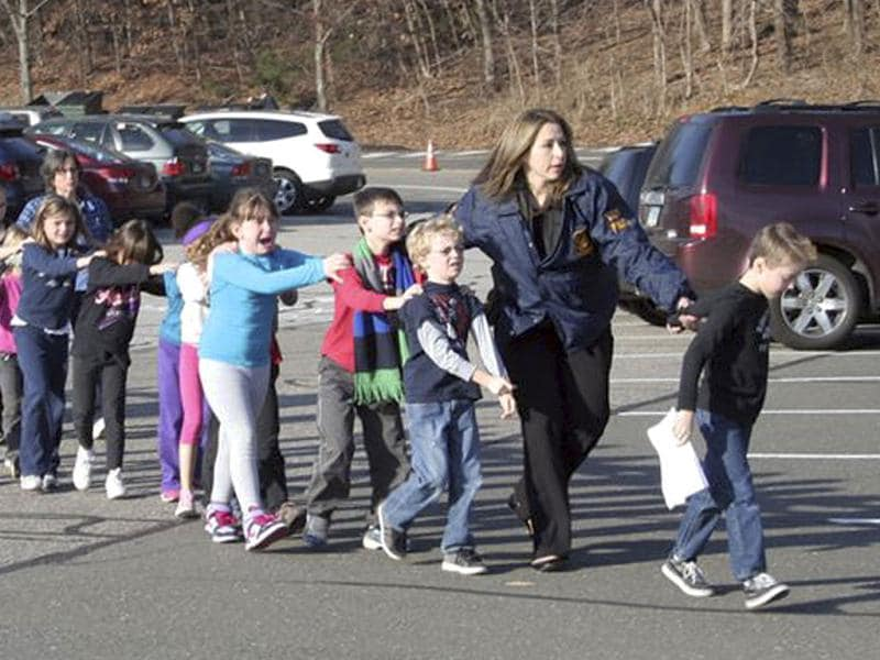 20 school children were slaughtered by a heavily armed gunman who opened fire at Sandy Hook Elementary School in Connecticut in the one of the worst mass shootings in US history. In this photo, Connecticut State Police lead children from the school following the shooting. AP/Newtown Bee