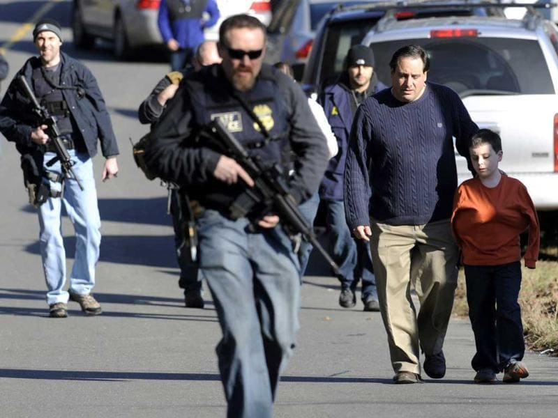 Parents leave a staging area after being reunited with their children following a shooting at the Sandy Hook Elementary School in Newtown, Connecticut, about 60 miles (96 kilometers) northeast of New York City. AP Photo/Jessica Hill