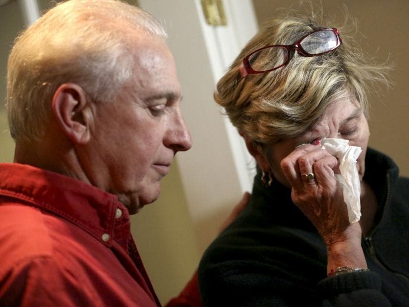 Ray Ruzek consoles Shirley Towne as she speaks of the events of the day before a prayer meeting at the Heaven Ice Cream shop in Newtown, Connecticut. A gunman walked into the school on Friday and opened fire, killing 28 people, including 20 children. AP photo