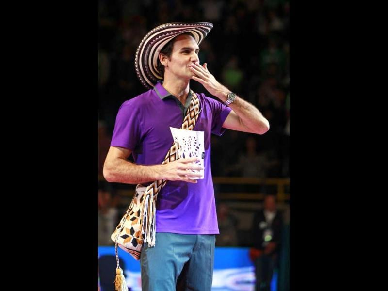 Roger Federer of Switzerland, wearing a Colombian Vueltiao, blows a kiss while holding his trophy after beating Jo-Wilfried Tsonga of France in an exhibition tennis match in Bogota. Reuters