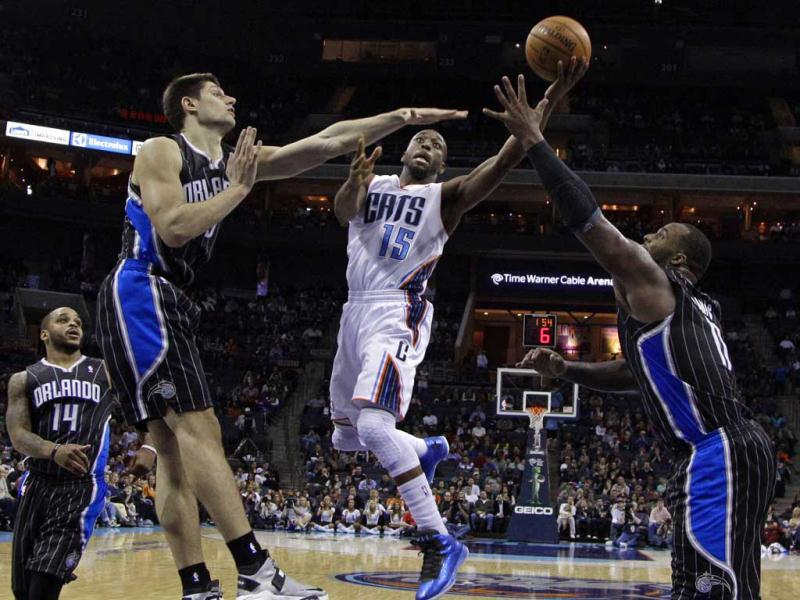 Charlotte Bobcats' Kemba Walker drives between Orlando Magic's Nikola Vucevic, left, and Glen Davis, right, during the second half of an NBA basketball game in Charlotte, N.C. The Magic won 107-98. AP photo