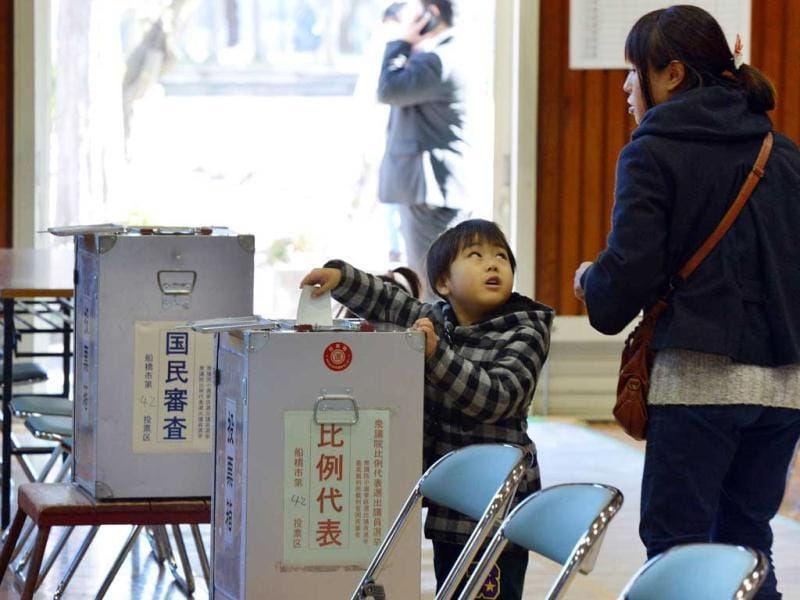A boy helps his mother (R) to cast a vote in the general election at a polling station in Funabashi, suburban Tokyo. Voters began casting ballots in Japan for a general election likely to return long-ruling conservatives to power after three years in the wilderness. AFP photo
