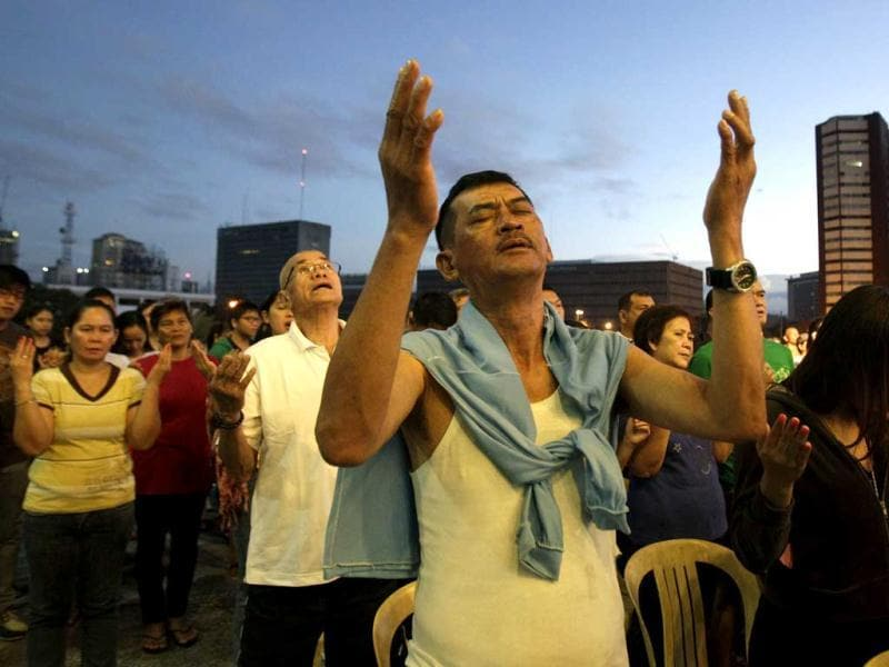 Filipino Catholics raise their arms during prayers as they attend the first dawn Mass at the Cultural Center of the Philippines building in Manila. AP