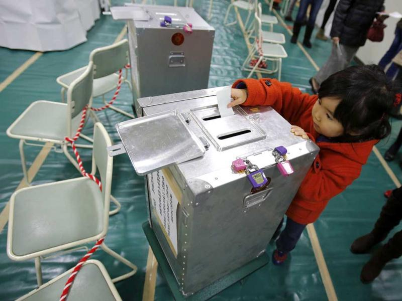 Haruka Tobe casts a ballot for her parents at a polling station located inside an elementary school in Tokyo. Reuters