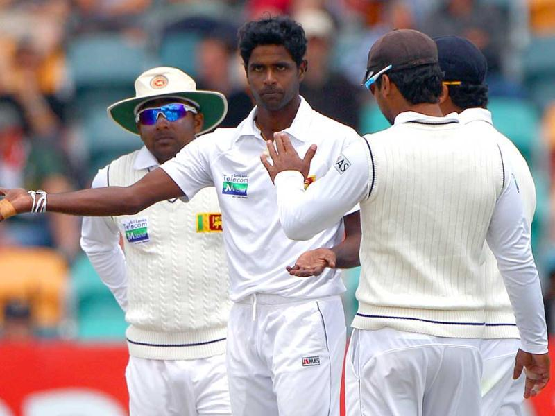 Sri Lanka's Shaminda Eranga, second from left, is congratulated by teammates after bowling Australia's Phil Hughes for 16 runs on the fourth day of their cricket test match at Bellerive Oval in Hobart, Australia. AP Photo