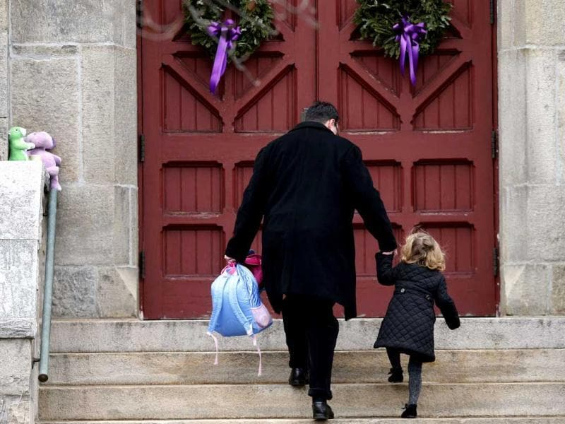 A man helps a young girl up the stairs while carrying her backpack as they arrive for services at Trinity Church in Newtown, Connecticut. A gunman walked into Sandy Hook Elementary School in Newtown Friday and opened fire, killing 26 people, including 20 children. AP photo