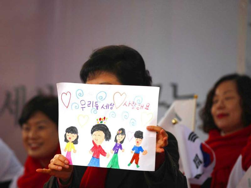 South Korea's presidential candidate Park Geun-hye of ruling Saenuri Party holds a painting drawn by a supporter's child, during her election campaign rally in Cheonan, south of Seoul. The Korean characters in painting reads