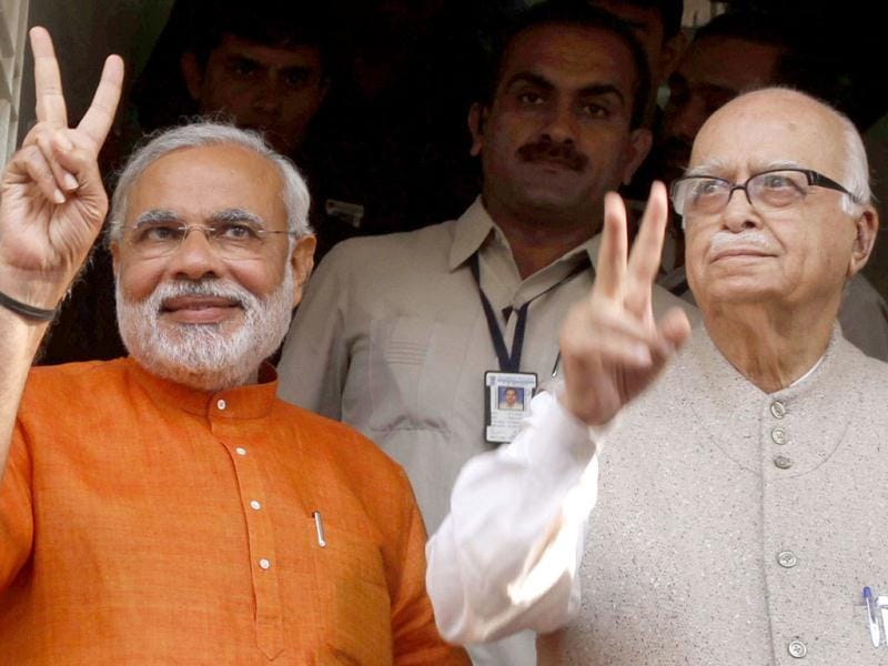 Gujarat chief minister Narendra Modi flashes a victory sign as he sees off BJP senior leader Lal Krishna Advani after a meeting at party's state head quarters in Ahmadabad. The second and last phase of Gujarat Assembly elections was held on Monday. (AP Photo)