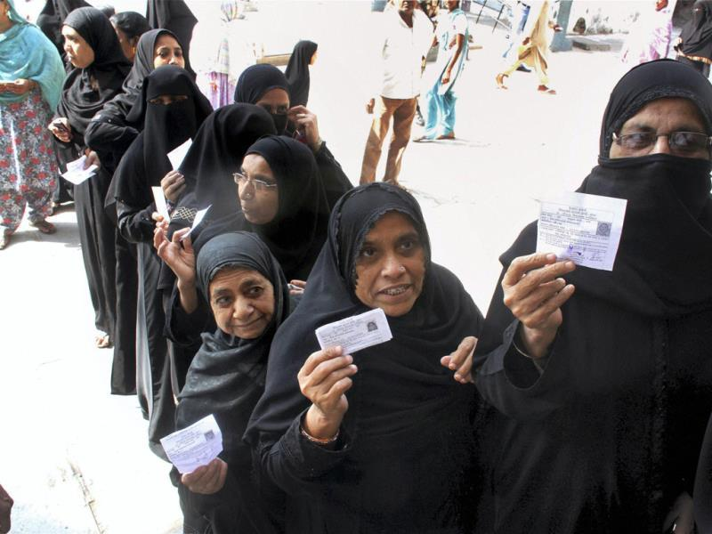 Women voters stand in a queue to vote at a polling station for the second phase of Gujarat Assembly elections in Ahmedabad. (PTI Photo)