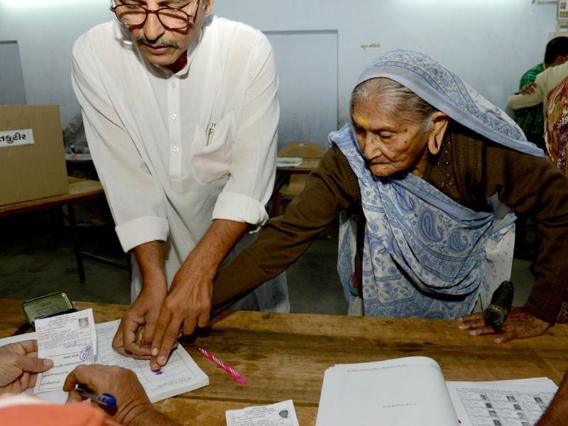 Elderly voter Ujamben Kanjibhai Dudhatra, who according to voter identity documents is 106 years old, makes a thumb imprint as she completes formalities before casting her vote for Assembly elections in Gujarat. (AFP Photo)
