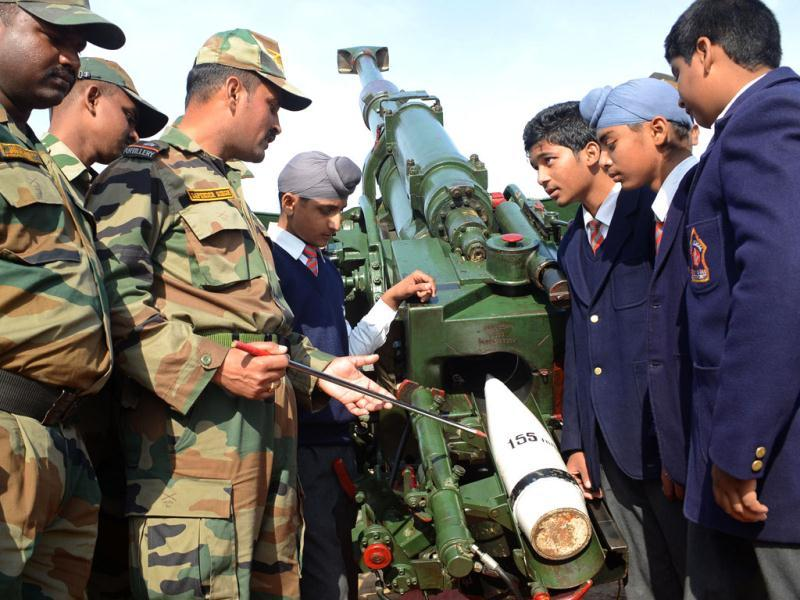Army officers and schoolchildren pose next to a 155/45 Soltam gun during an Army Mela (fair) and exhibition at Khasa, some 15 kms from Amritsar. The Army Mela (fair ), organised by the Vajra Corps, displayed weapons, tanks, aircraft and military equipment to students and civilian visitors of the event. AFP PHOTO/ NARINDER NANU