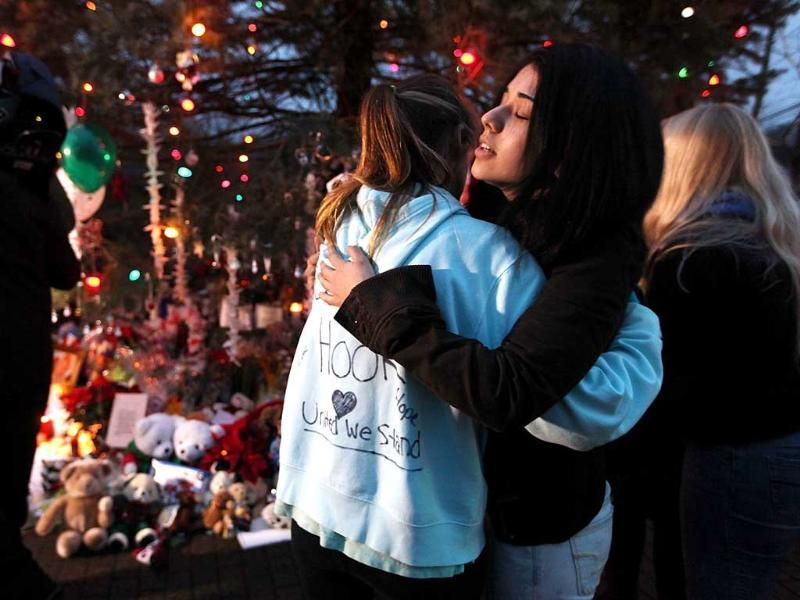 People hug at a memorial for victims of the mass shooting at Sandy Hook Elementary School, in Newtown, Connecticut. AFP Photo
