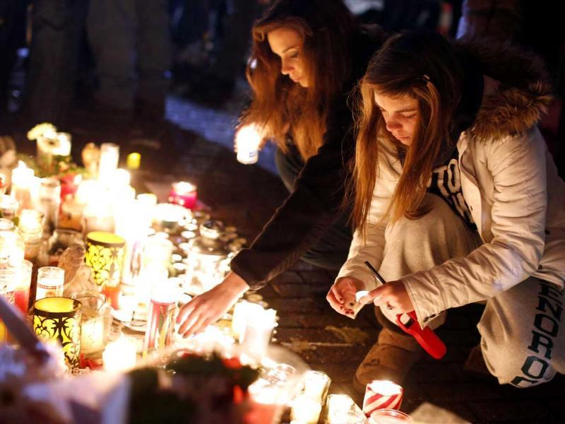 Visitors light candles at a memorial to shooting victims in Newtown. AP Photo/Jason DeCrow