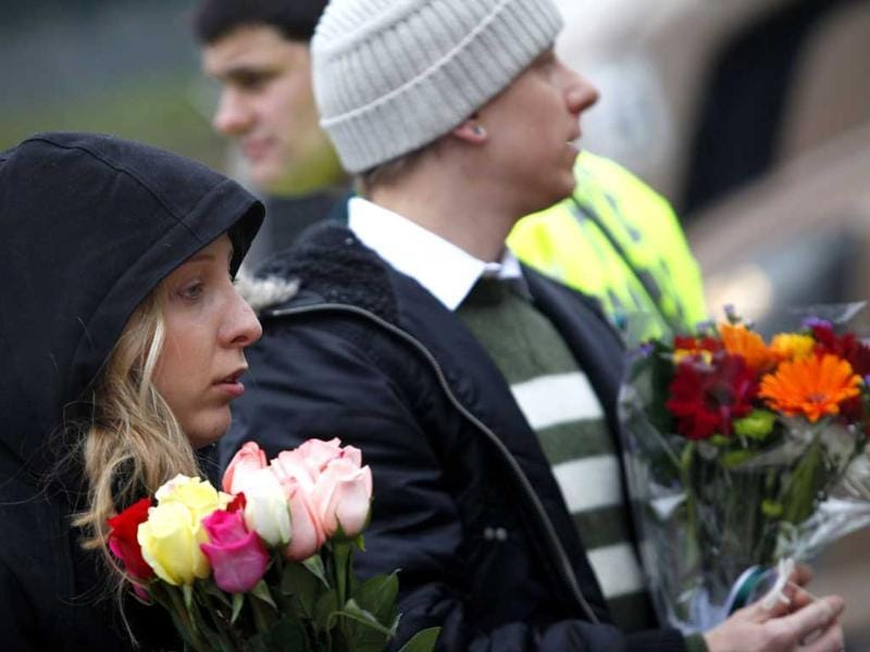 A couple carries flowers to a makeshift memorial in Newtown, Connecticut. Reuters/Joshua Lott