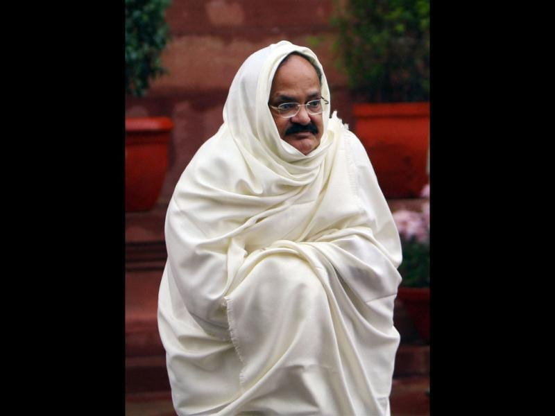 BJP MP Venkaiah Naidu wraps a shawl to beat the cold on a rainy day during Parliament's winter session in New Delhi. PTI Photo by Kamal Singh