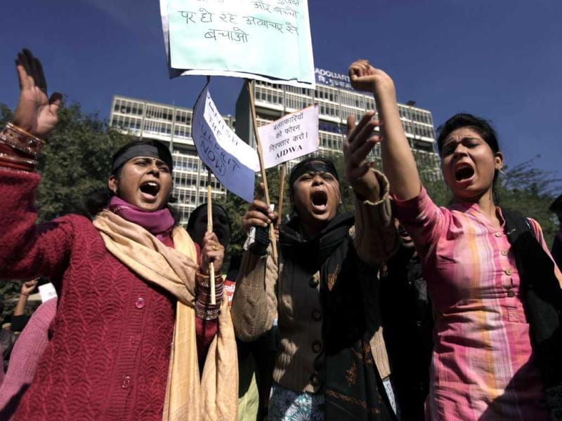 Women shout slogans outside the Delhi Police HQs as they block main road during a protest. The Sunday gang-rape and near fatal beating of a 23-year-old student on a bus triggered outrage and anger across the country as people demanded action from authorities. The placard at center right reads