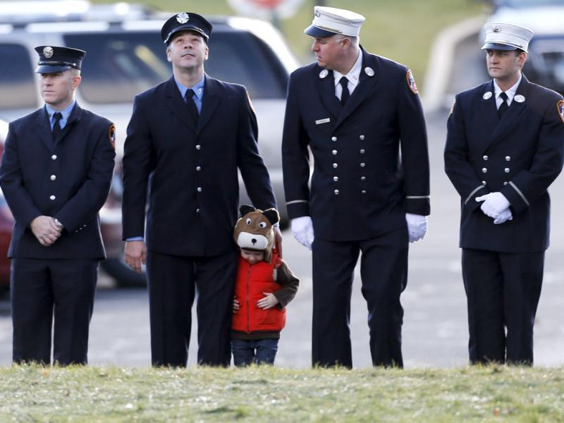 A child lines up with firefighters outside the funeral for school shooting victim Daniel Gerard Barden at St. Rose of Lima Catholic Church in Newtown, Connecticut. AP Photo