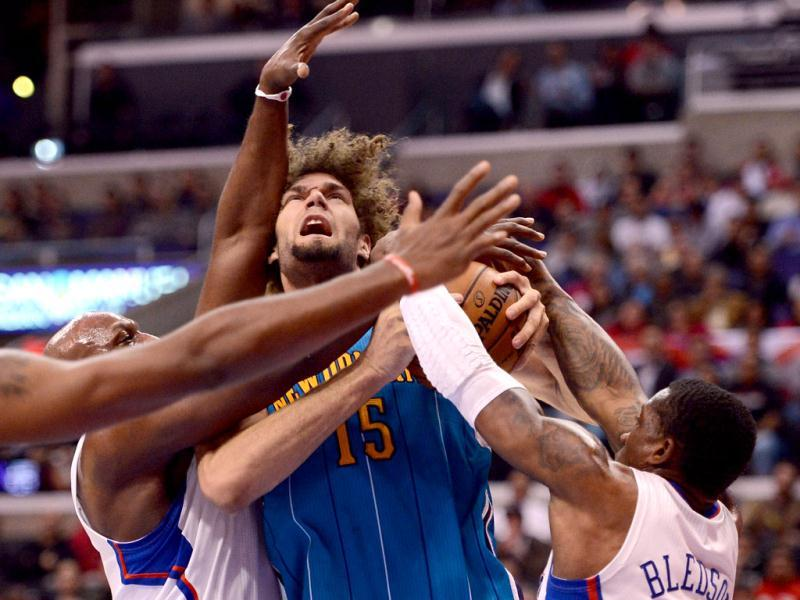 Robin Lopez #15 of the New Orleans Hornets is surrounded by Lamar Odom #7 and Eric Bledsoe #12 of the Los Angeles Clippers as he attempts a shot at Staples Center in Los Angeles, California. AFP Photo