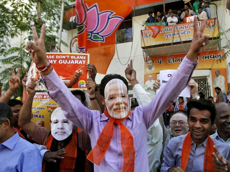 Supporters of Bharatiya Janata Party (BJP) wear masks of Gujarat chief minister Narendra Modi as they celebrate to early reports that their party is leading in the Gujarat assembly elections in Ahmadabad. AP Photo/Ajit Solanki