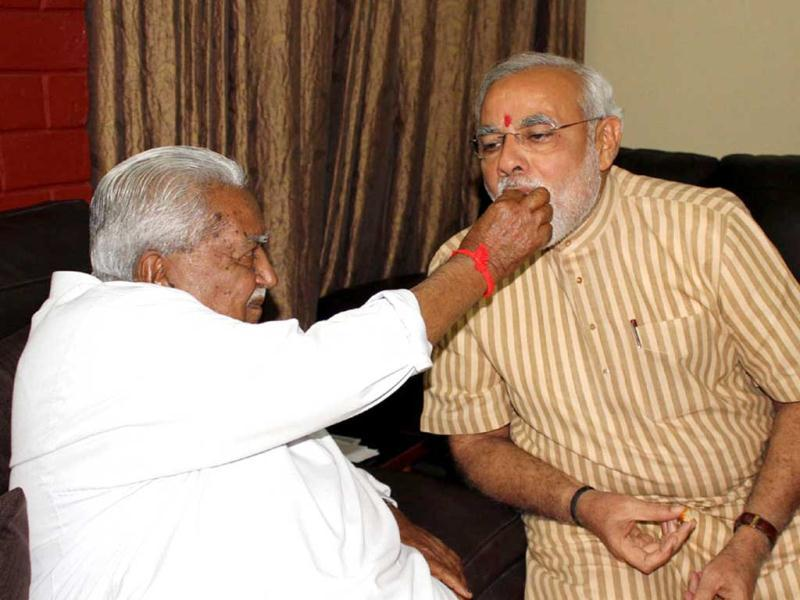 GPP president Kesubhai Patel offers sweets to Gujarat chief minister Narendra Modi at Gandhinagar after victory in Gujarat Assembly polls. (UNI Photo)